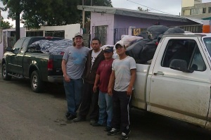 Wayne with a couple of our team members in TJ.  We just unloaded the bags you see in the white truck from the green truck.